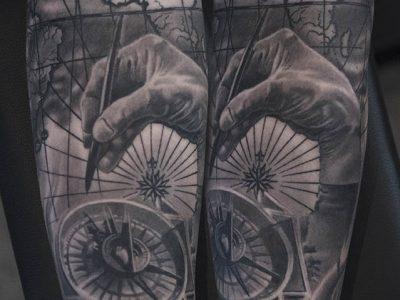black and grey tattoo, realism tattoo, surrealism tattoo , smooth shading tattoo, compass and map realistic tattoo tattoo, nautical tattoo, navigation tattoo, hand holding compass tattoo
