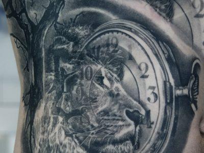 Black and grey tattoo, best black and grey tattoo, smooth shading tattoo, portrait tattoo , lio ntattoo, pocket watch tattoo, surrealistic tattoo, pocket watch and lion tattoo, surrealistic tattoo, realism tattoo, jungle tattoo, wild life tattoo, Unique art tattoo, photorealism tattoo, High details tattoo, ribcagetattoo,